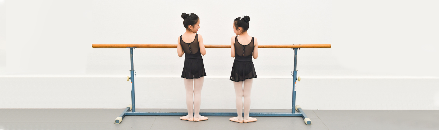 two girls standing infront of a ballet bar in first position